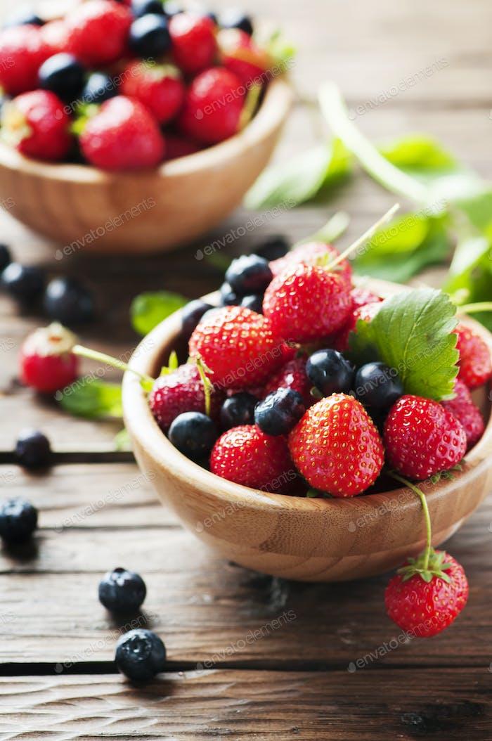 Rote süße Erdbeere und Heidelbeere auf dem Holztisch