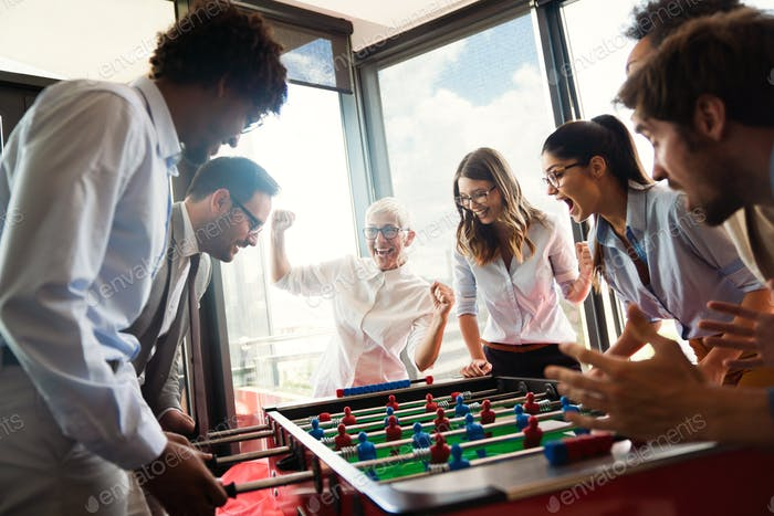 Business people having great time together.Colleagues playing table football in modern office