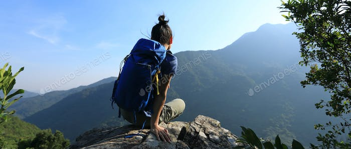 Thinking woman hiker sit at mountain top cliff edge