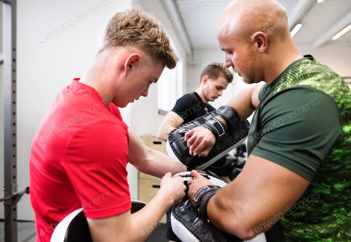Fit young man in gym with his trainer preparing for boxing.