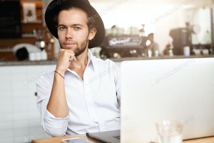 Gut aussehender junger Selbständiger mit Bart sitzt im Café vor modernem Laptop, wieder