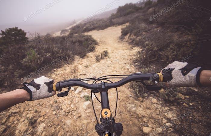 Downhill pov view with mountain bike