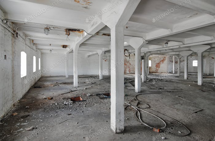 Empty industrial room of an old abandoned factory with white columns