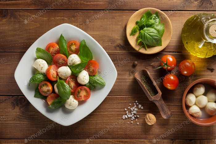 caprese salad and ingredients at wood