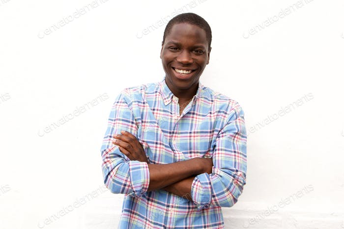 Smiling young african man with arms crossed standing against white background