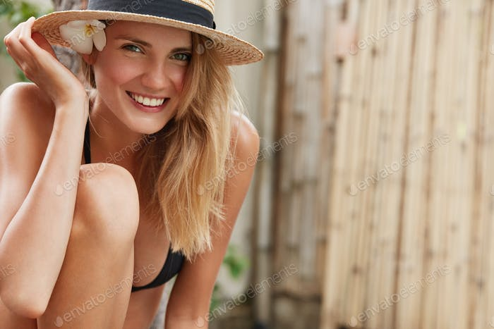 Happy adorable woman in straw hat and bathing suit, feels satisfied to have good summer rest in trop