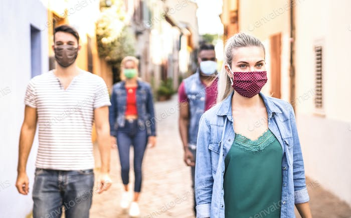 Multiracial friends walking with face mask after lockdown reopening