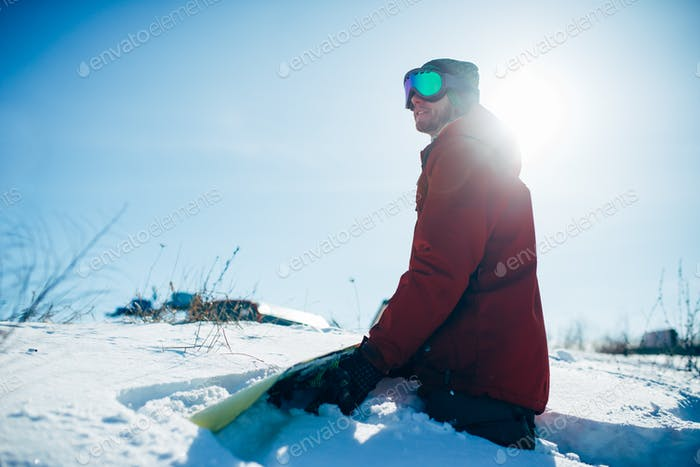 Snowboarder sitting on snowy slope in sunny day