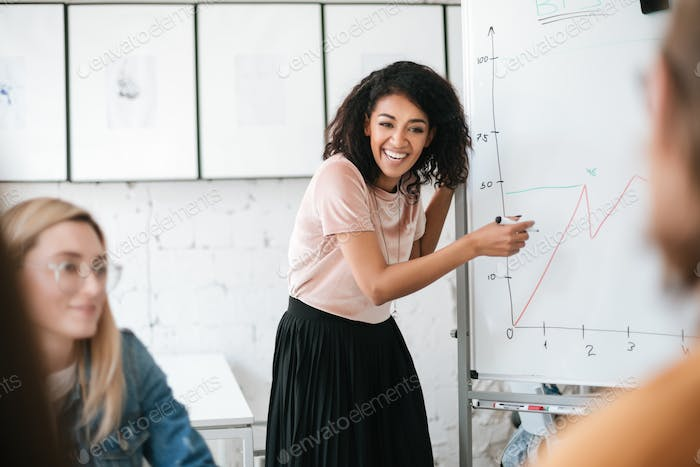 Cheerful African American young girl standing near board and giving presentation to colleagues