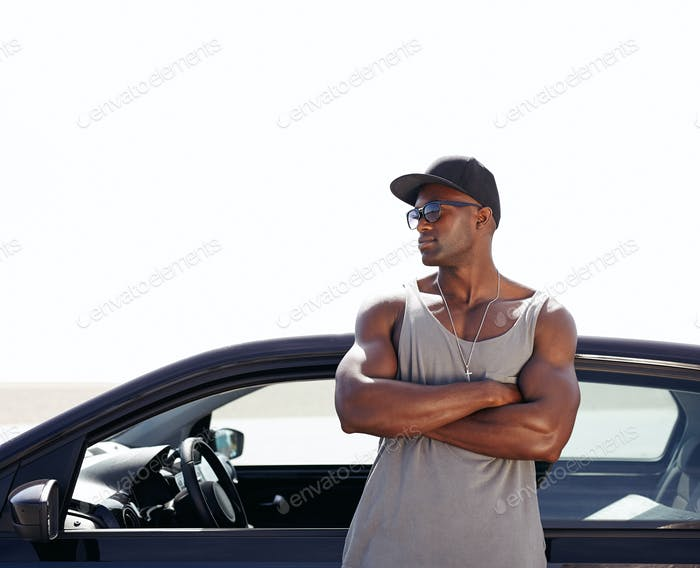 Muscular african man standing by his car