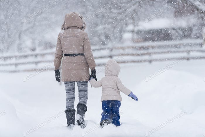 Mother with her little girl in snow