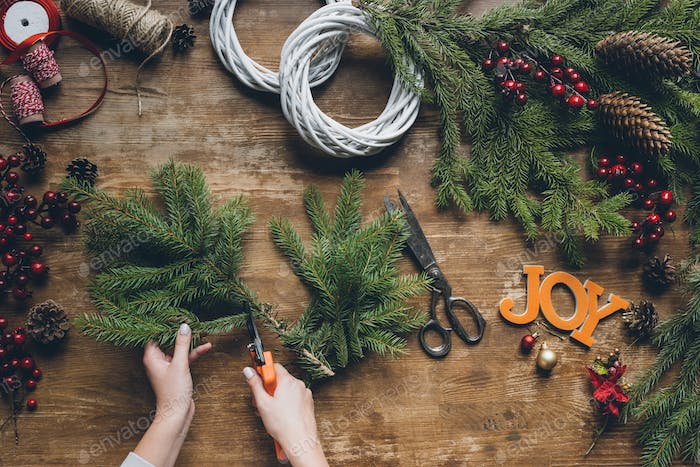 top view of florist hands making Christmas wreath with word Joy on wooden tabletop