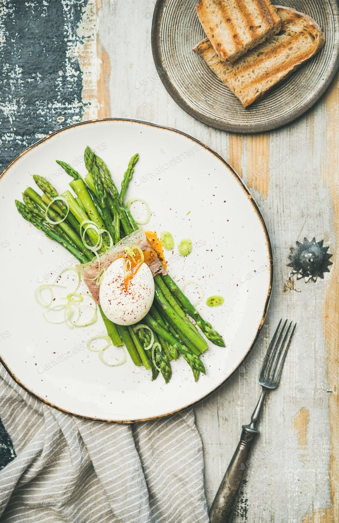 Flat-lay of green asparagus, soft-boiled egg , bacon and toasts
