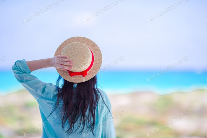 Young woman in hat on a tropical beach looking on the beautiful sea