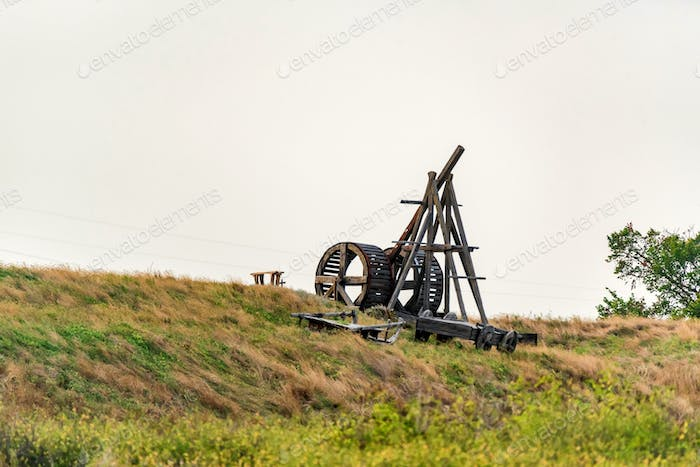 Old wooden catapult against grey sky background