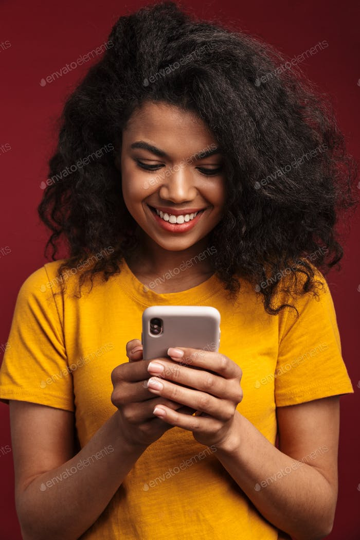 Image of brunette african american woman smiling and using cellphone