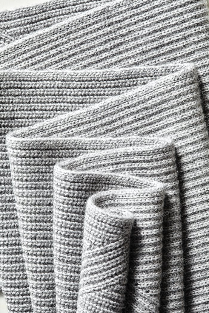 Draped melange gray woolen knitted fabric as background.