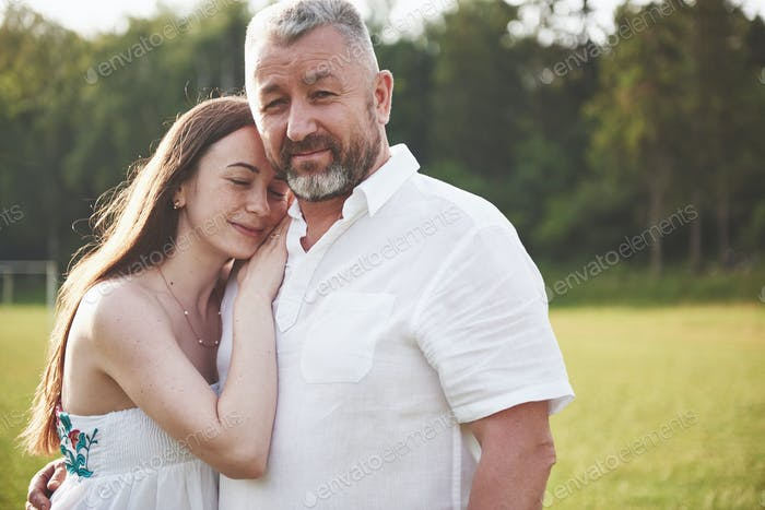 An elderly man hugged his adult daughter outdoors