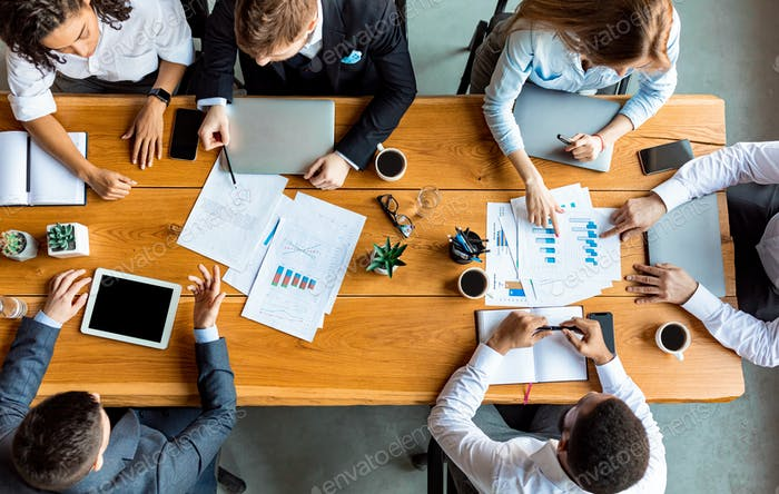 Mixed Business Team Working Sitting At Table In Office, Above-View
