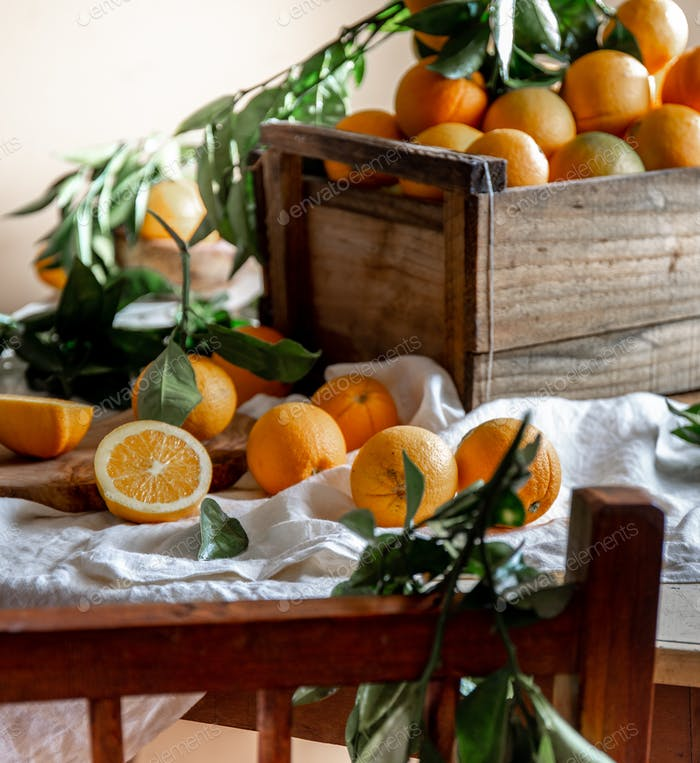 Box of orange fruit, with green leaves and orange juice on the table. Home gardening