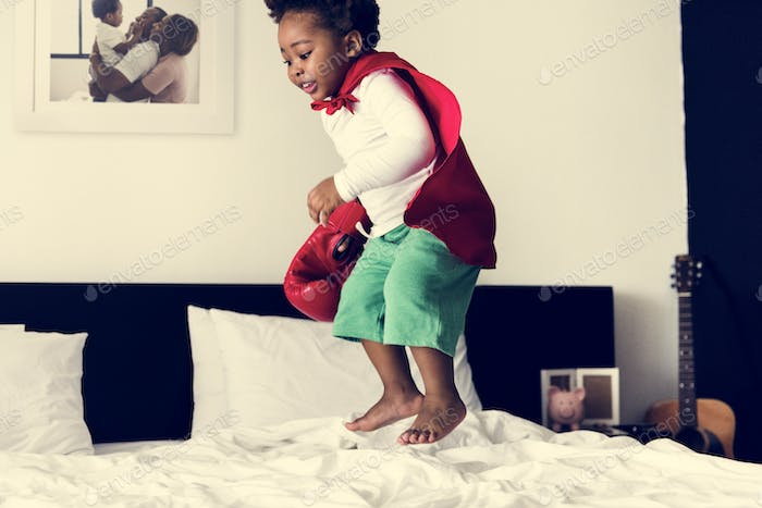 African descent kid jumping on the bed