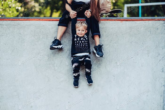 Beautiful young hipster mom holds her little son by the hands