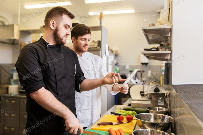 two chefs cooking food at restaurant kitchen