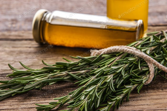 Rosemary with blurred olive oil on the wooden table