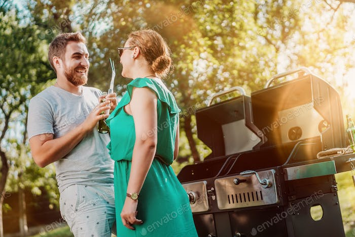 Portrait of perfect caucasian couple laughing at barbecue party, friends having a good time