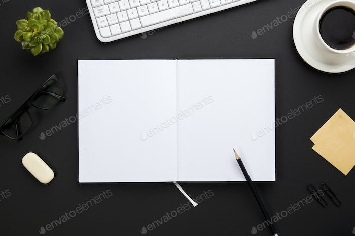 Blank Paper Surrounded By Office Supplies On Gray Desk
