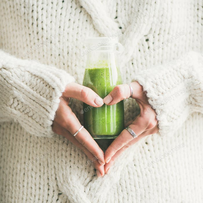 Winter seasonal smoothie drink detox in woman's hands, square crop