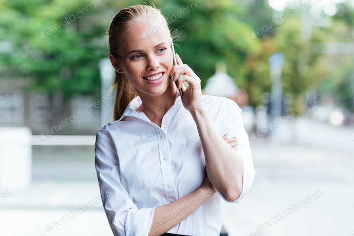 Portrait of a cheerful young businesswoman with mobile phone