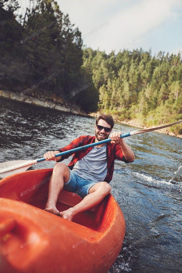 Junger Kerl Kanu auf einem See