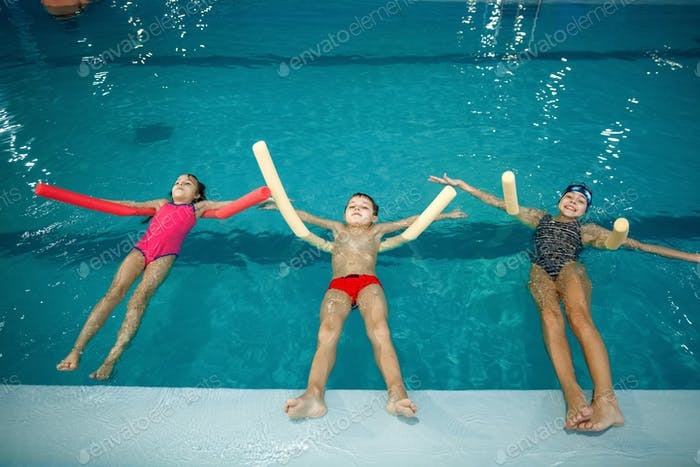 Children swimming group lies on back in the pool