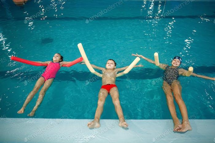 Kinderschwimmgruppe liegt auf dem Rücken im Pool