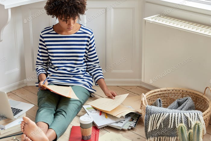 Talented female architect involved in working process, sits bare foot on wooden floor, reads informa