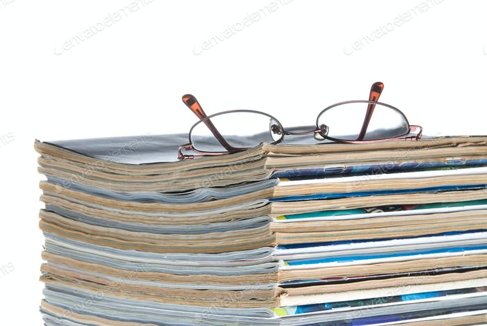 Stack of old magazines & reading glasses