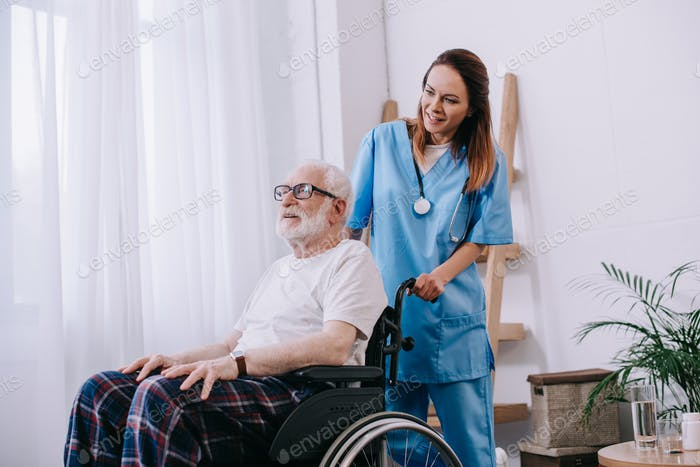 Enfermera empujando silla de ruedas con hombre mayor
