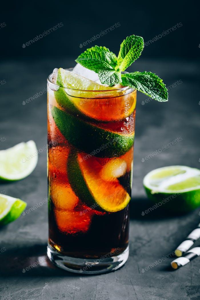 Rum und Cola Cuba Libre eiskalter Drink Cocktail mit Limette und Minze