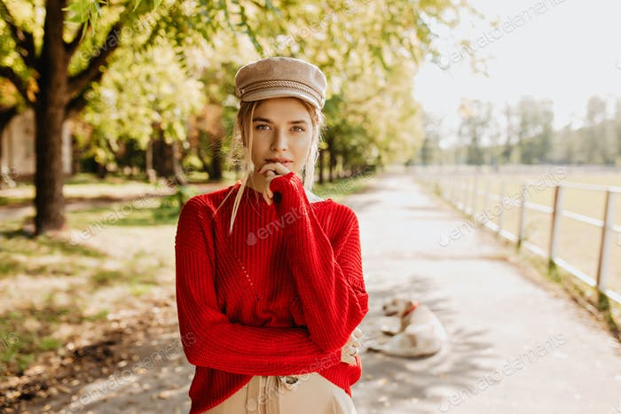 Beautiful young woman in red sweater and nice trendy hat looking thoughtful in autumn park. Attract