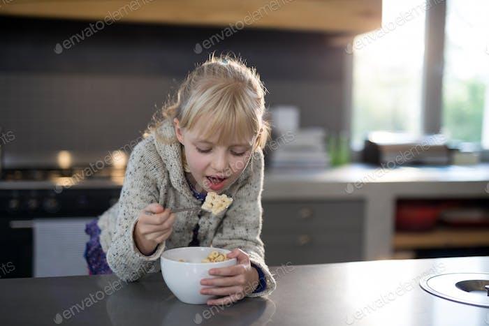 Kleines Mädchen essen Getreide Ringe mit Löffel aus einer Schüssel