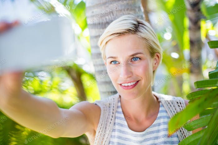 Pretty blonde woman taking selfie in the park