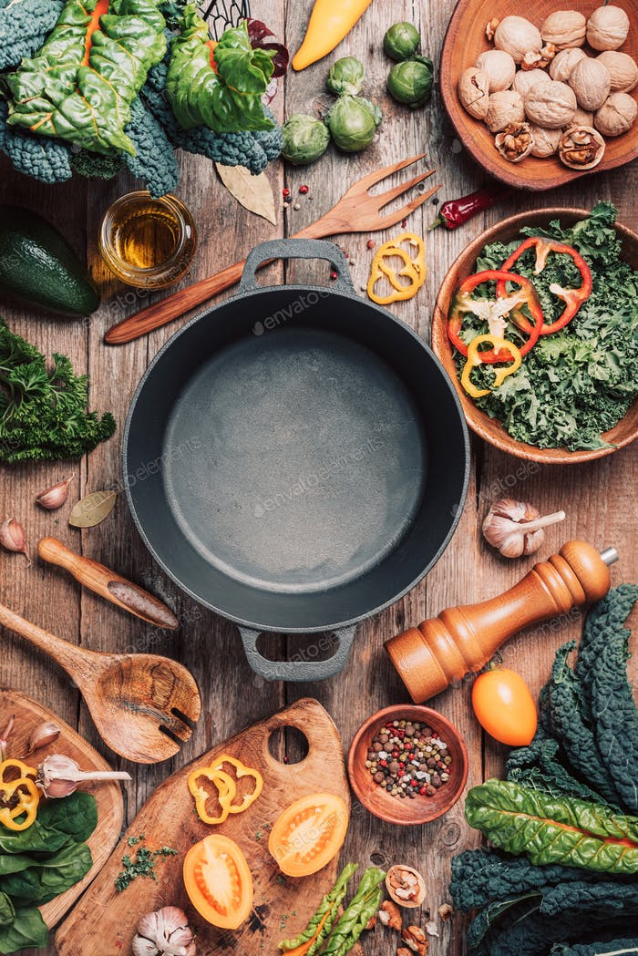Various organic vegetables ingredients and empty iron cooking pot, wooden bowls, spoons on wooden