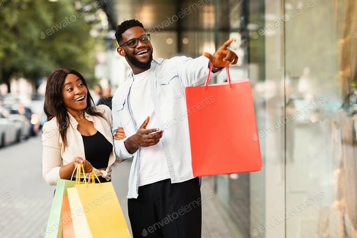Excited black couple with shopping bags pointing at window