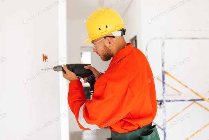 Young foreman in orange work clothes and yellow hardhat using el