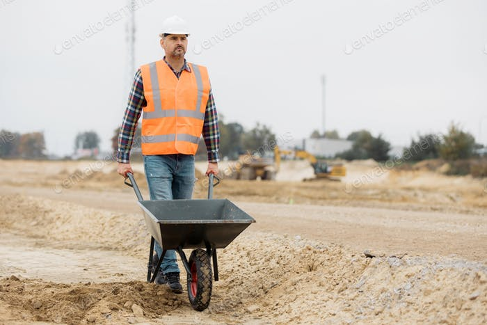 Handsome builder in an orange reflective vest leading a wheelbarrow throw road construction field