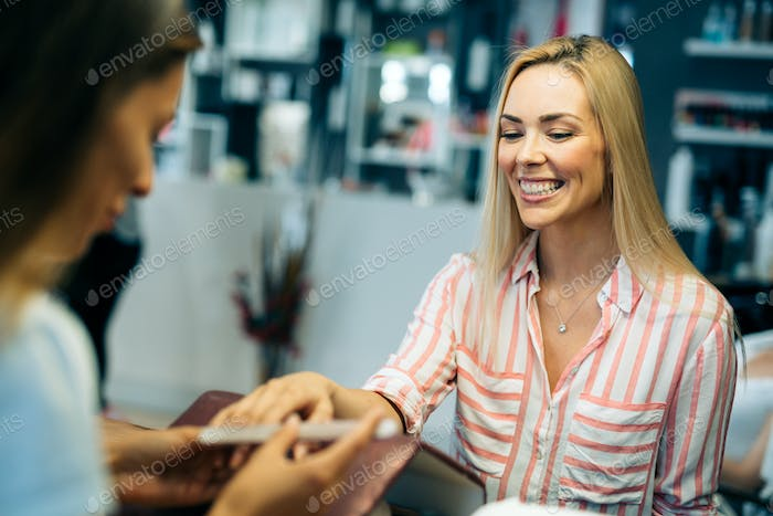 Gorgeous young woman getting her nails done by a manicurist
