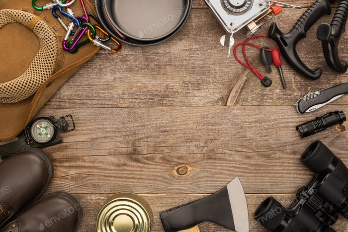 top view of camping equipment on wooden table with copy space