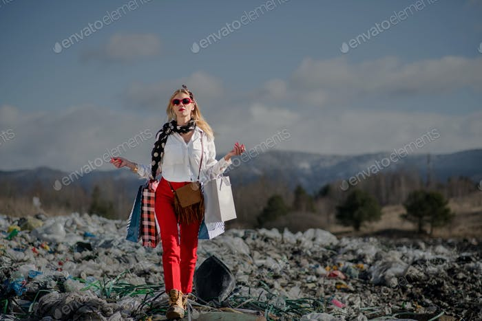 Woman with shopping bags on landfill, consumerism versus pollution concept