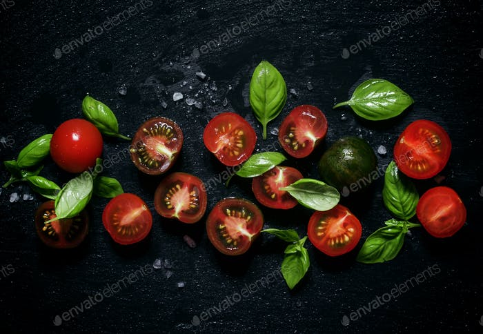 Red and black halves of tomatoes with green leaves of basil